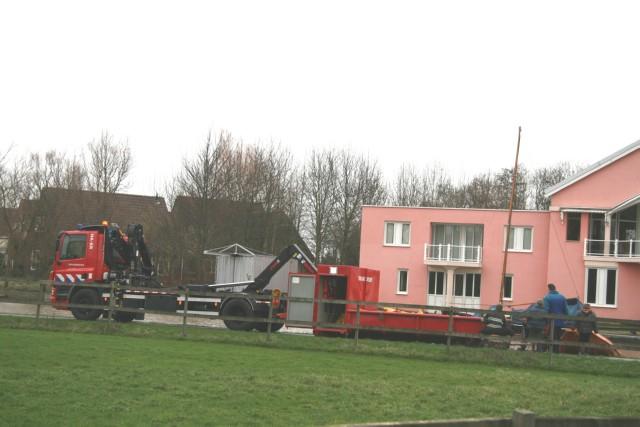 Brandweer plaatst olieschermen om gezonken boot.