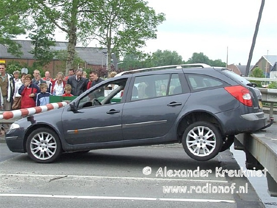 Brugwachter opent brug met auto erop