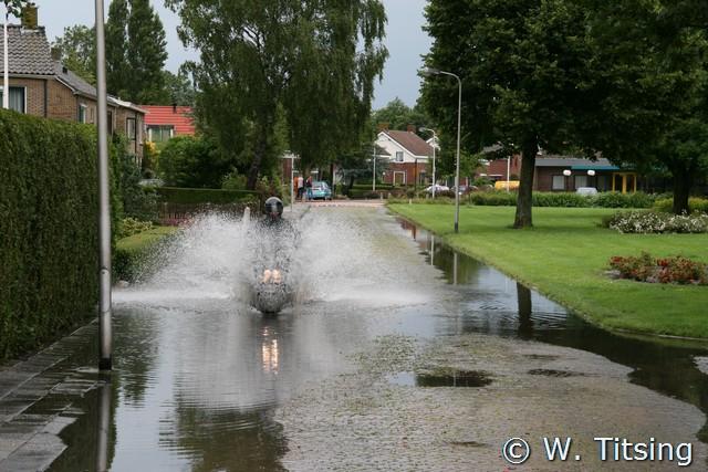Huis en straat blank na hevige regenval