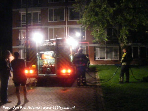 Bootje in brand achter flat