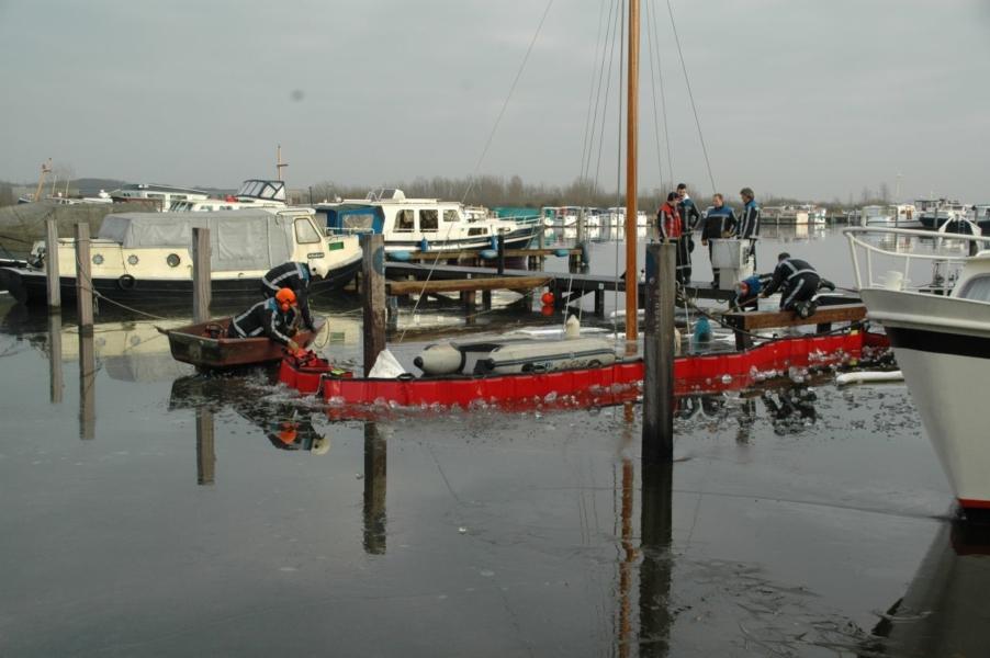 Brandweer plaatst oliescherm in haven St. Nicolaasga
