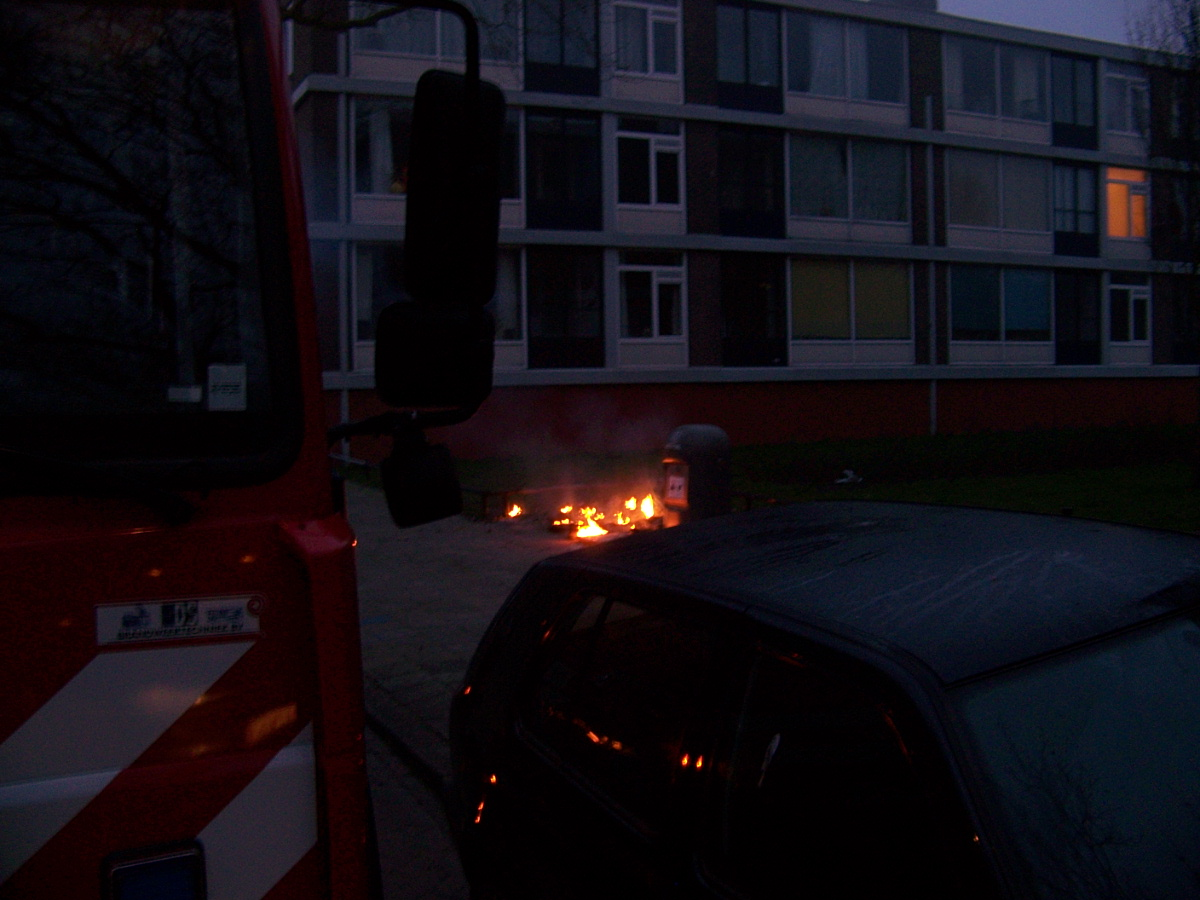 Afval naast container in brand