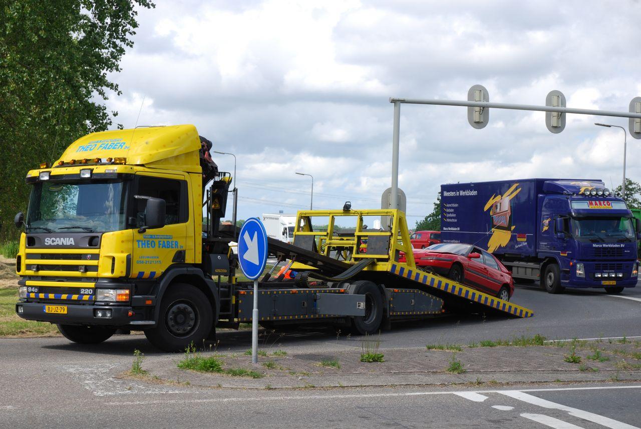 Vrachtwagen botst achterop personenauto voor stoplicht