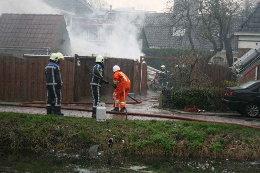Caravan in brand achter woning