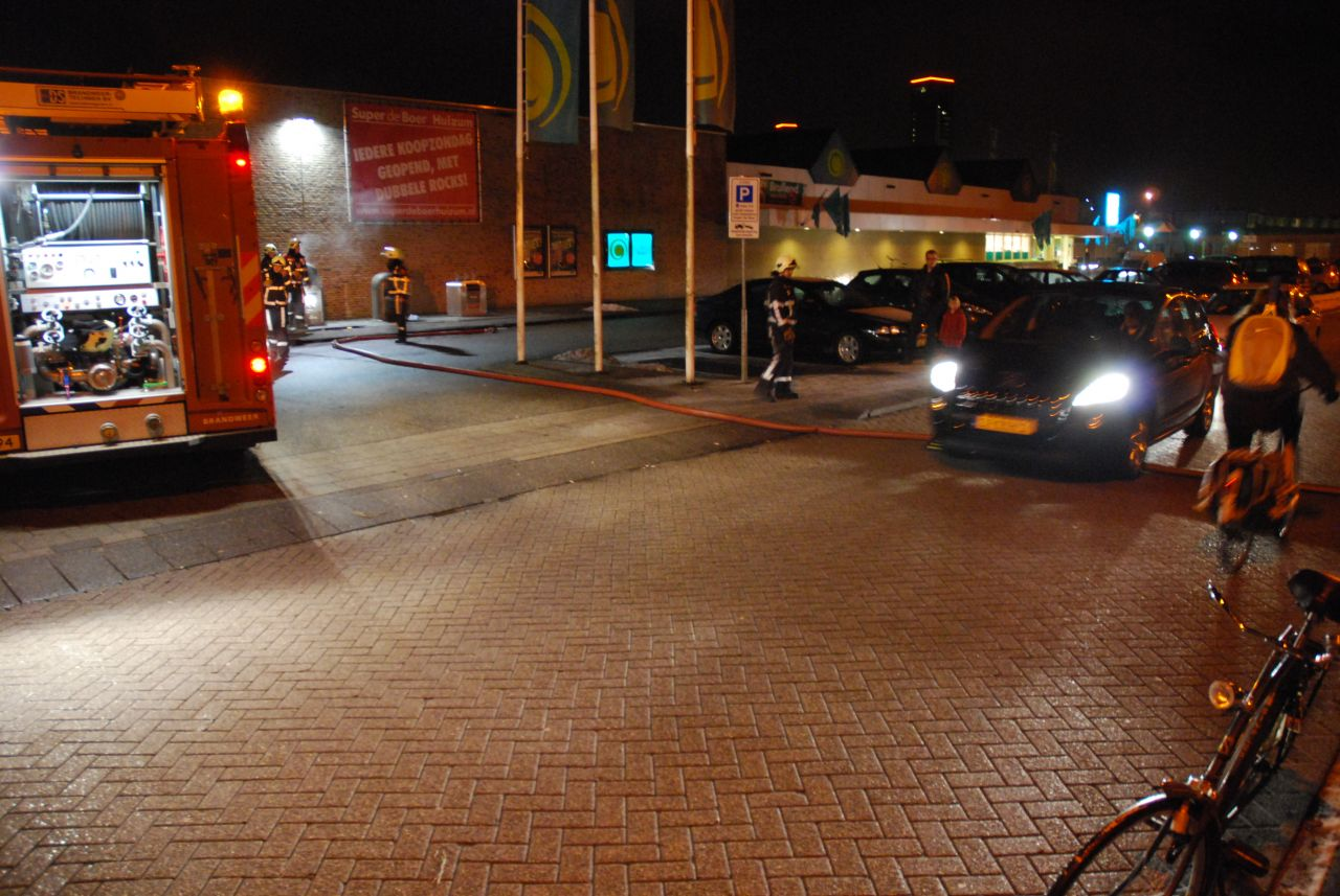 Containerbrand naast supermarkt