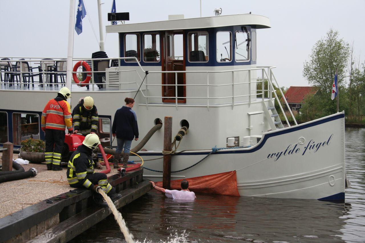 Brandweer pompt lek schip leeg