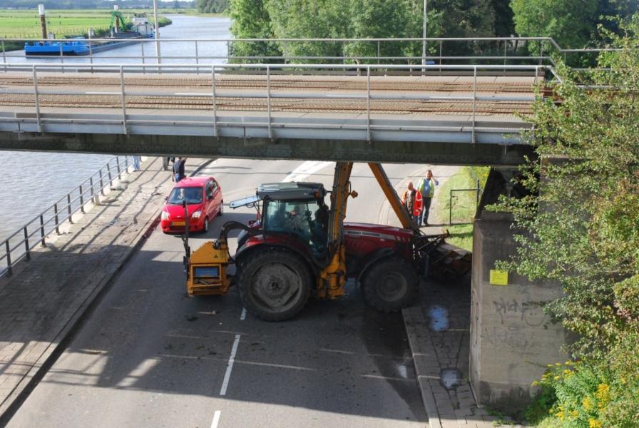 Tractor vast onder spoorbrug