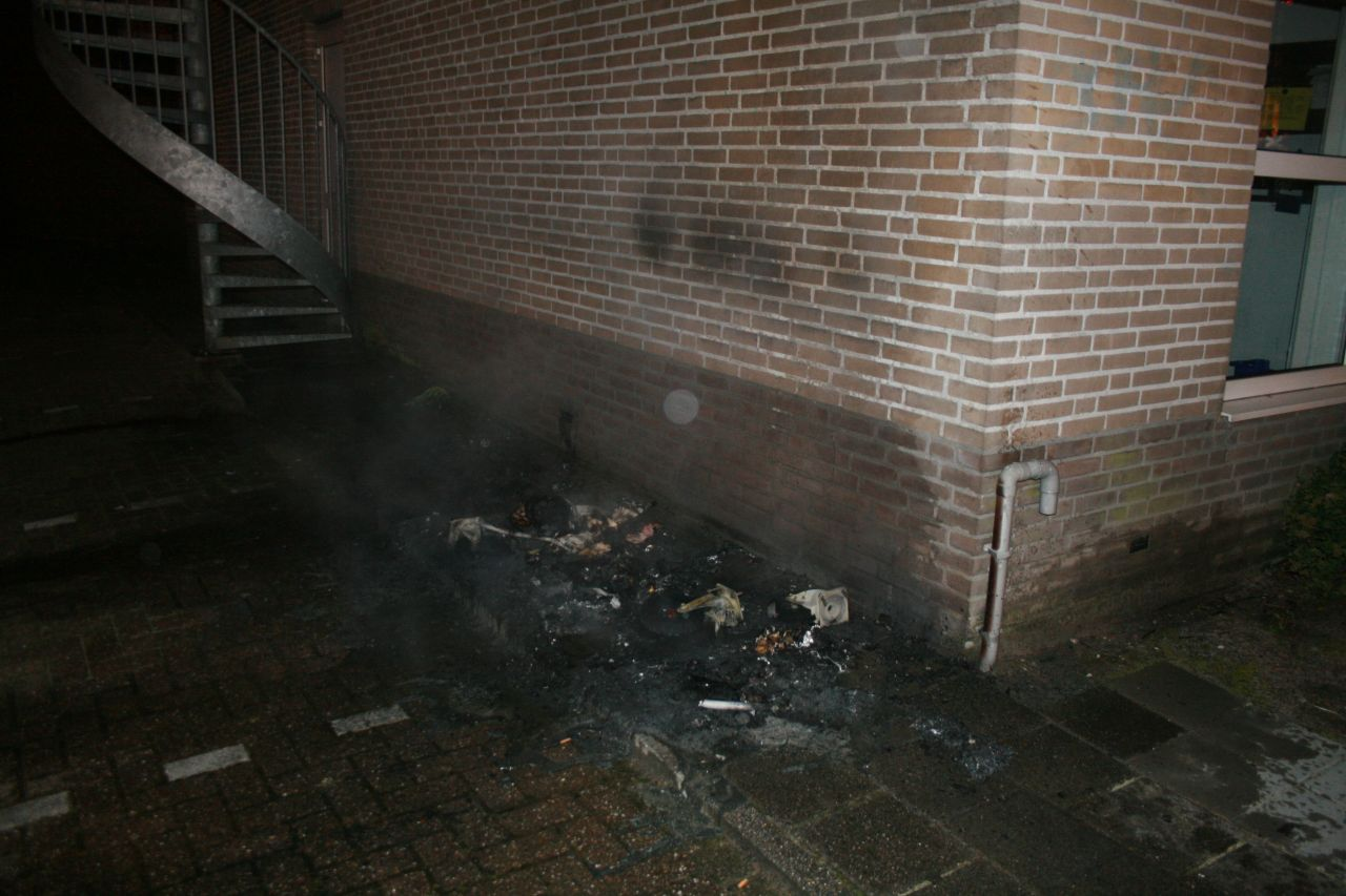 Container in brand tegen gevel Randstad