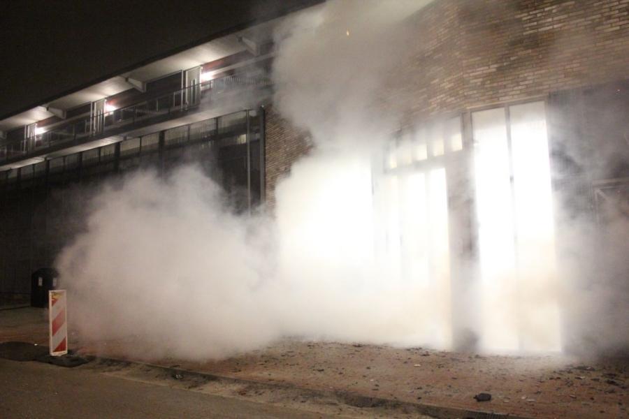 Afvalbrand tegen winkelcentrum aan