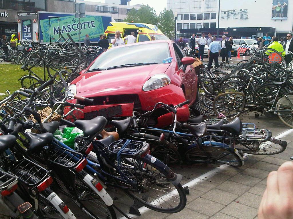 Auto rijdt over fietsenrekken
