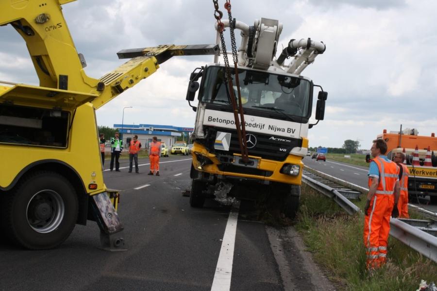 Vrachtwagen met betonpomp botst op rijdende wegafzetting