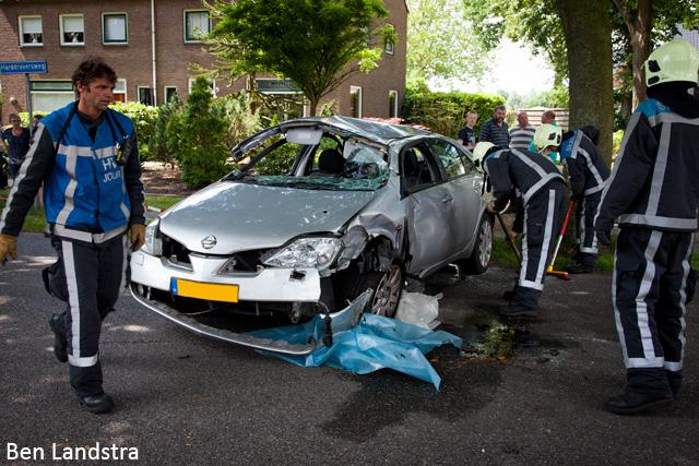 Auto op zijkant na botsing met boom