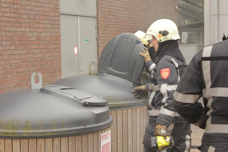 Container tegen gevel in brand