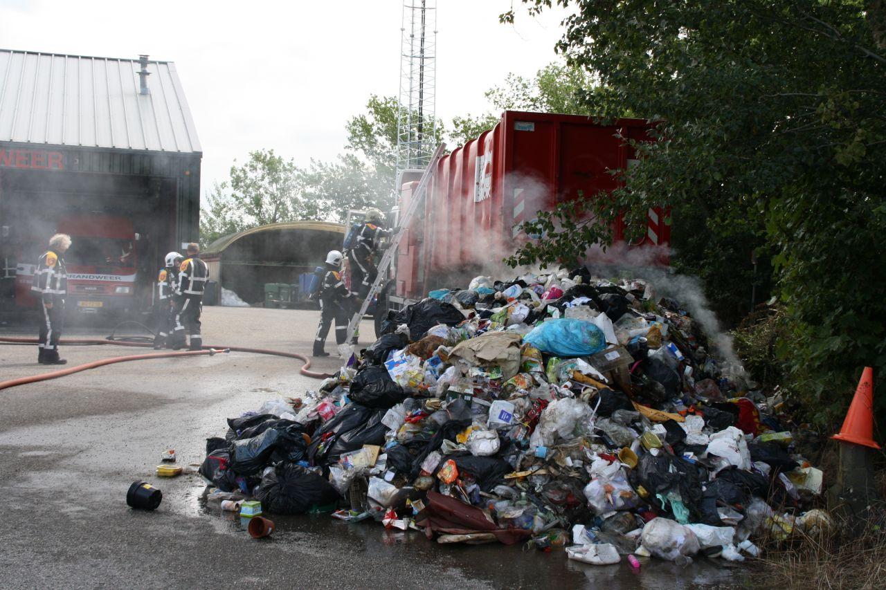 Vrachtwagen met huisvuil in brand voor kazerne