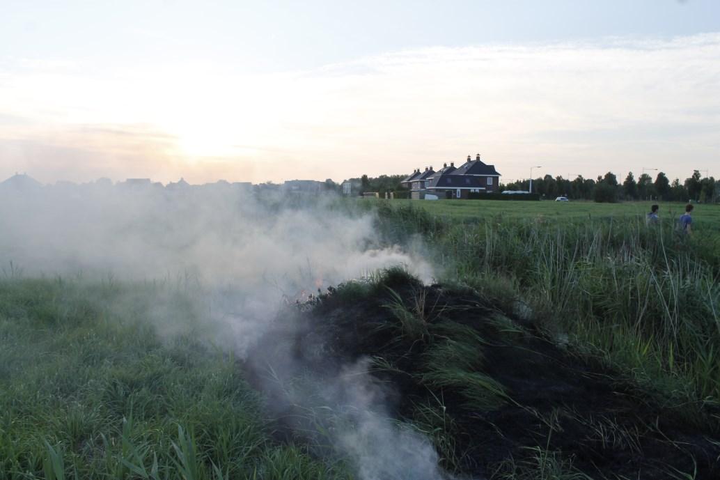 Buurtbewoner blust een brandende bult gras
