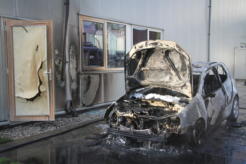 Auto tegen bedrijfspand in brand