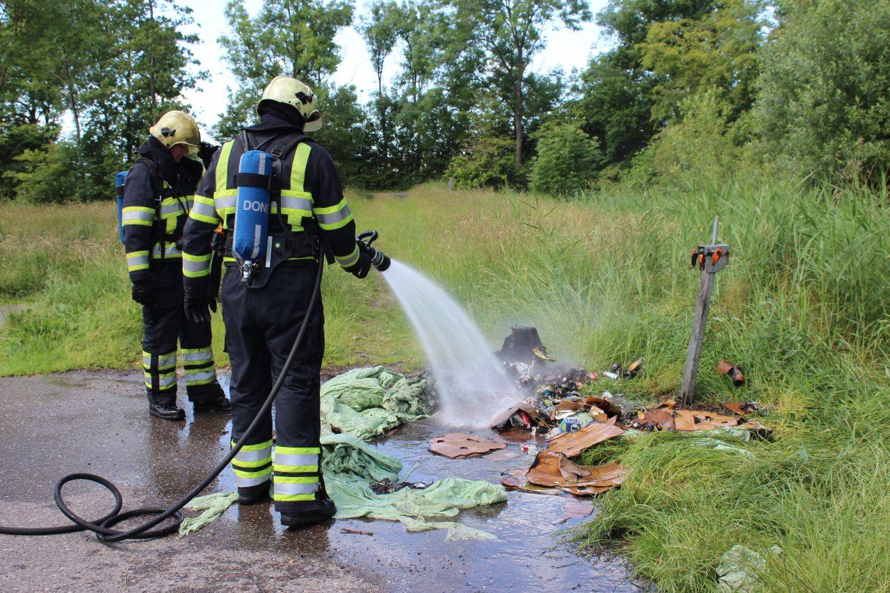 Brandweer blust containerbrand op parkeerplaats
