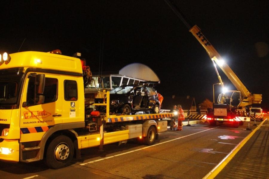 Auto schiet door hekwerk brug