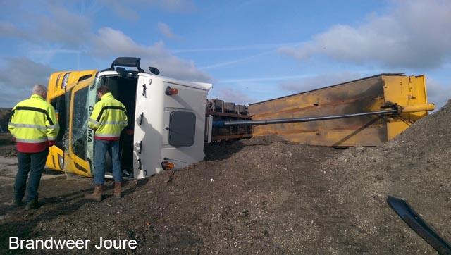 Vrachtwagen gekanteld op vuilstort