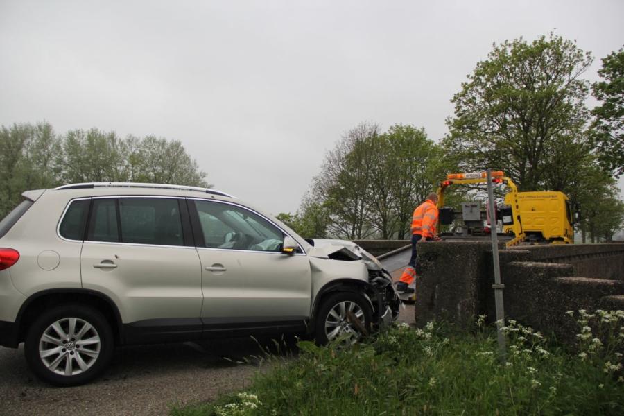 Auto botst tegen betonnen muurtje van brug