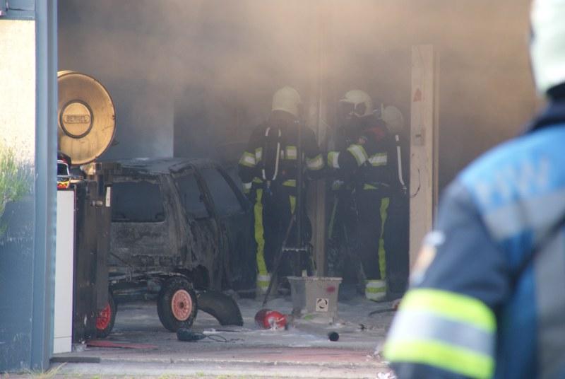 Auto in brand in garagebedrijf
