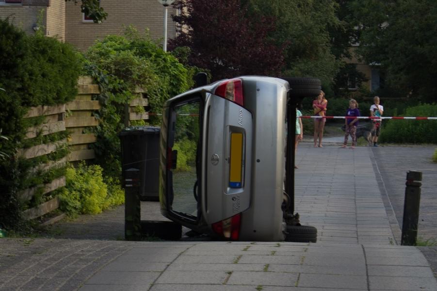 Auto op zijkant in woonwijk