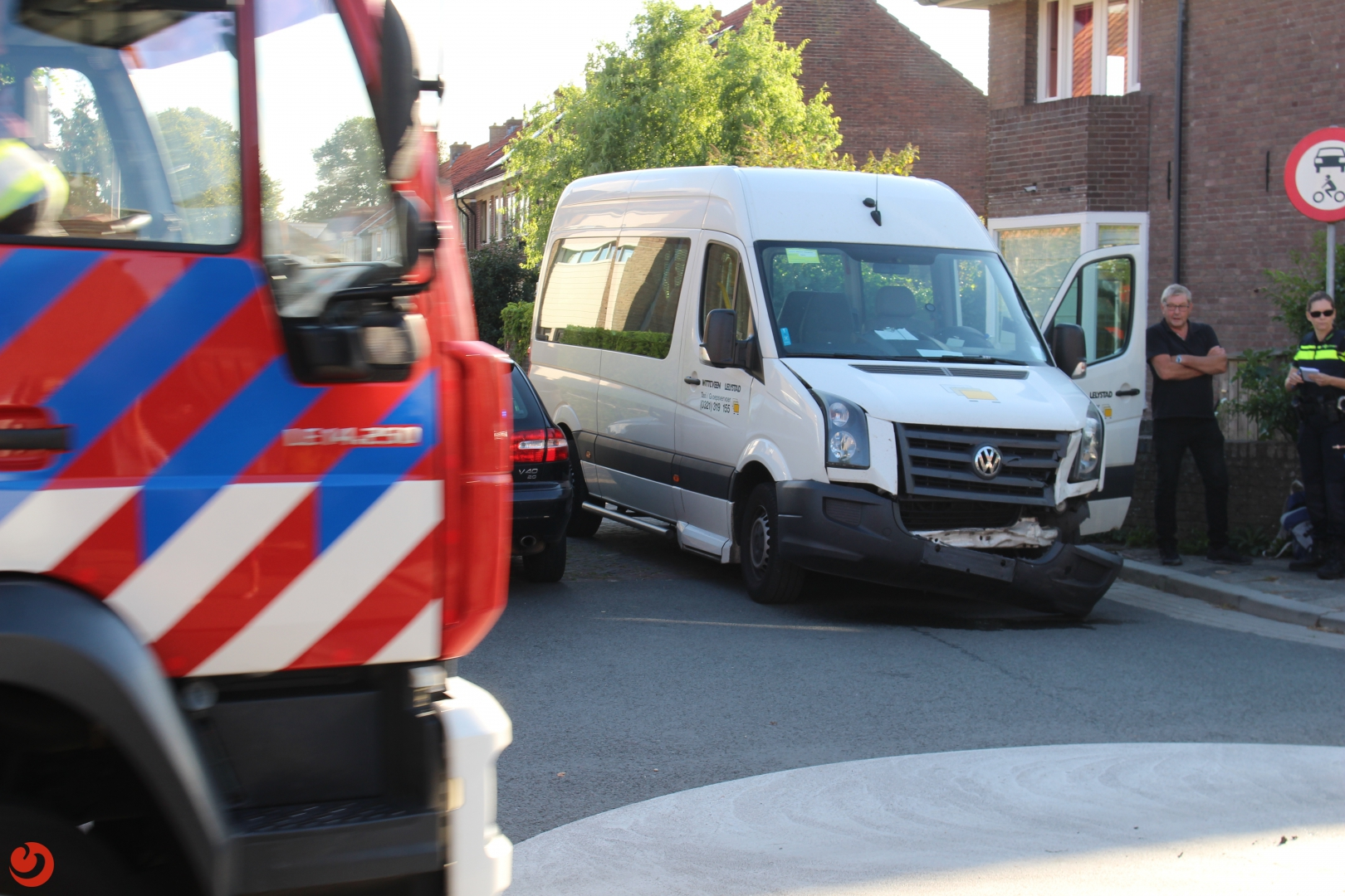 Taxibus en auto botsen in woonwijk