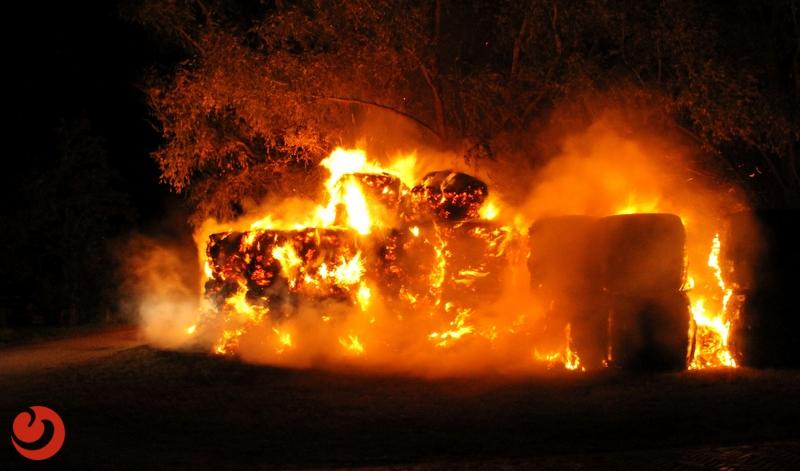 Forse brand in grote stapel hooibalen