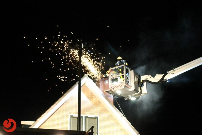 Brandweer met flex het dak op bij schoorsteenbrand