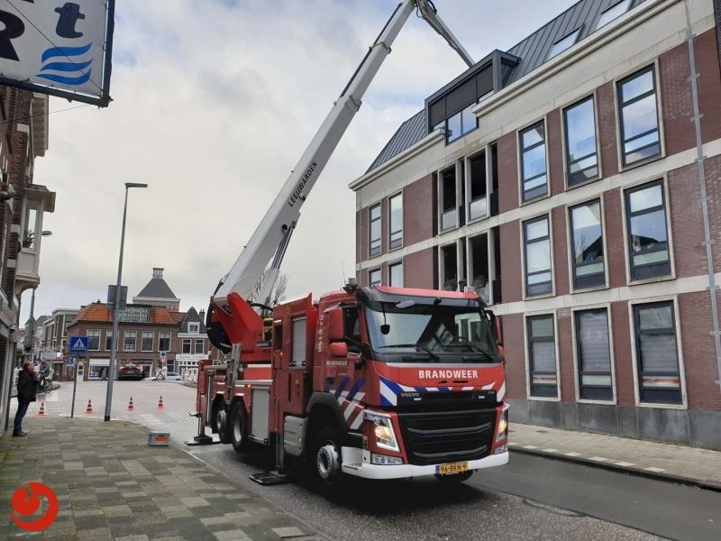 Brandweer zet losgewaaide pijp op dak weer vast