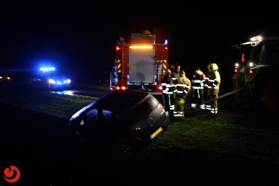 Auto hangt met bestuurster boven sloot