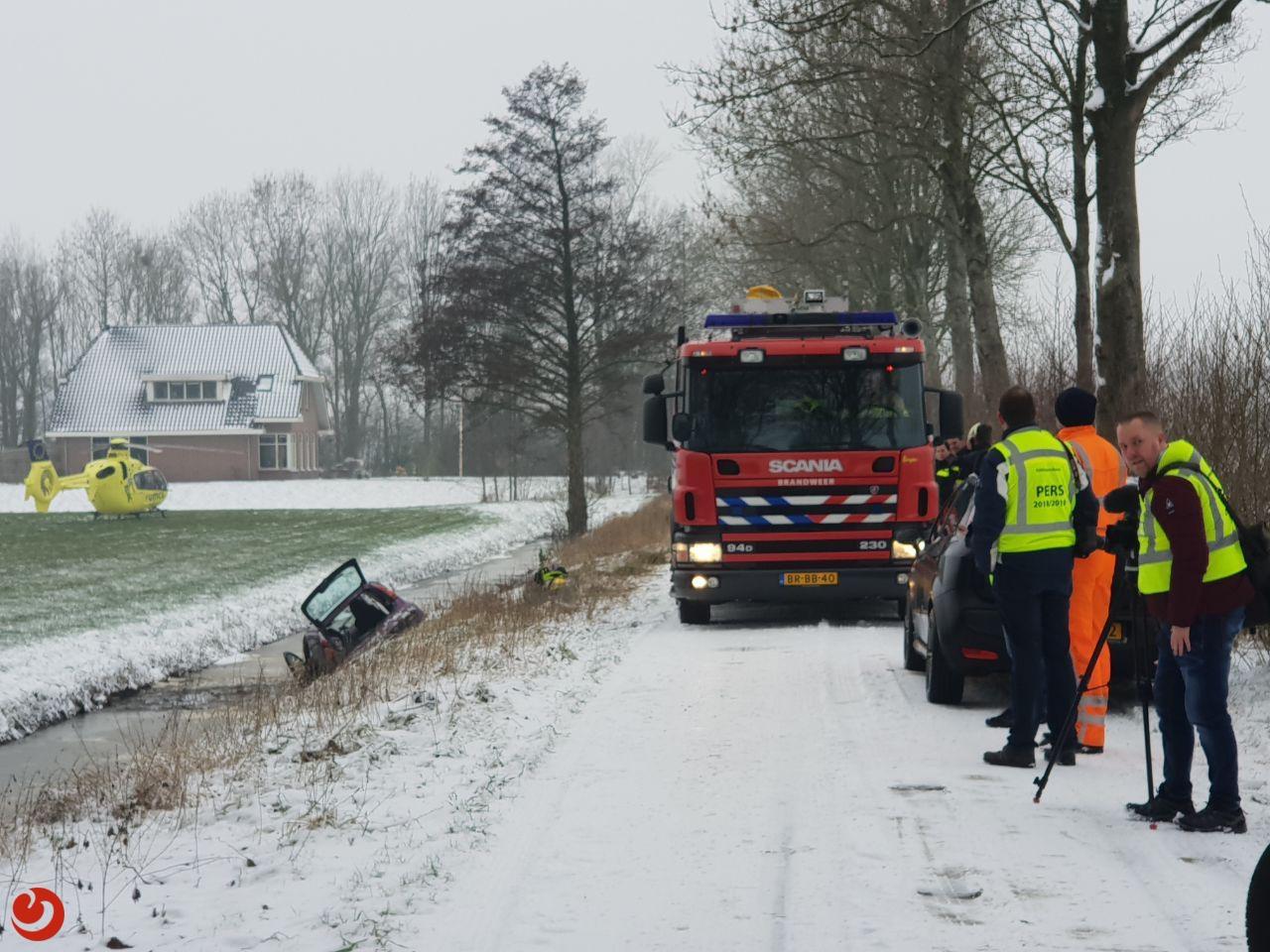 Auto op zij in sloot: bestuurder bekneld