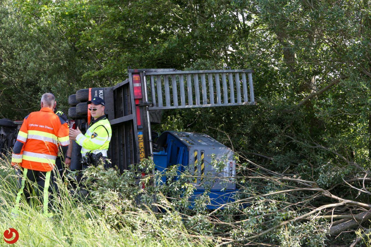 Vrachtwagen geladen met kraan zijwaarts in sloot