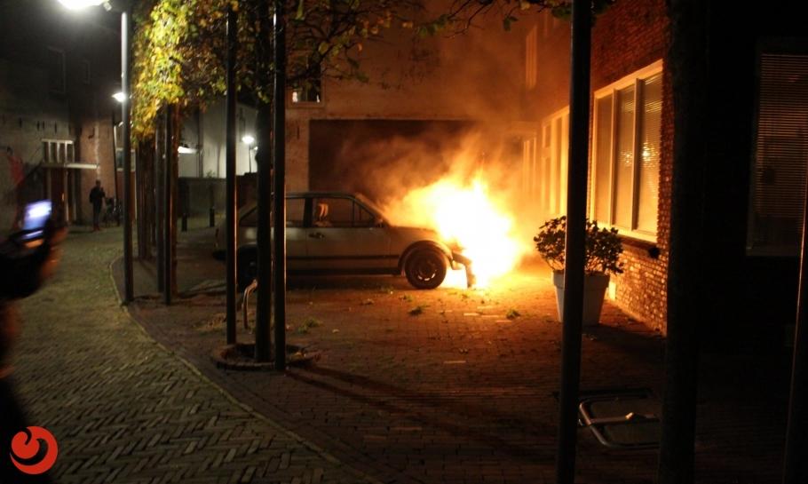 Auto in brand nabij gevel