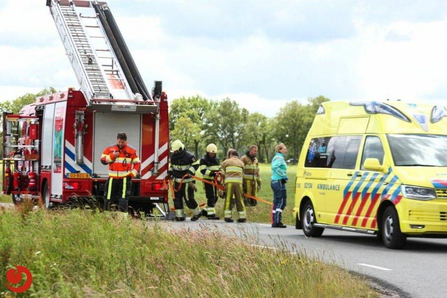 Brandweer helpt man uit te water geraakte auto