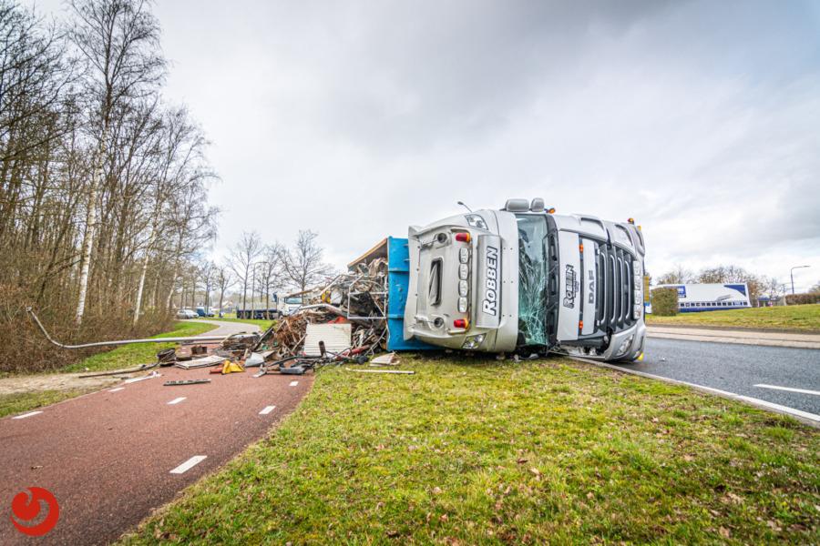 Vrachtwagen met schrootafval gekanteld op rotonde N351