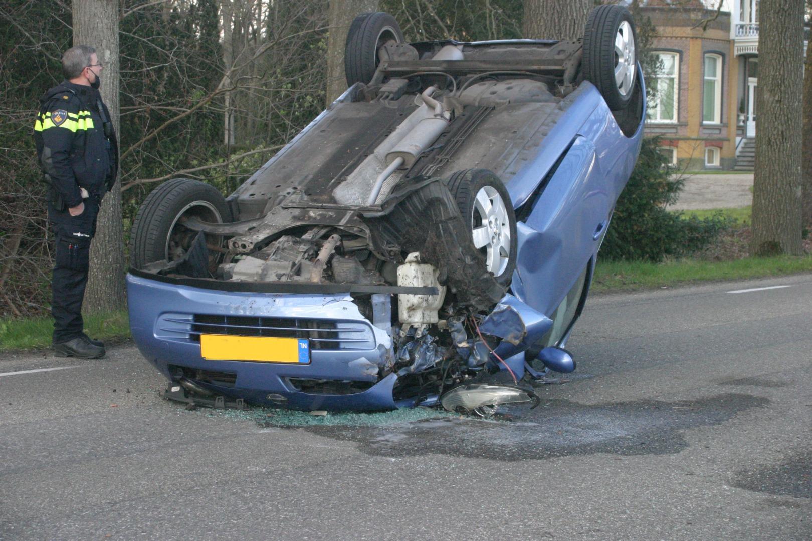 Auto op de kop na aanrijding met boom.