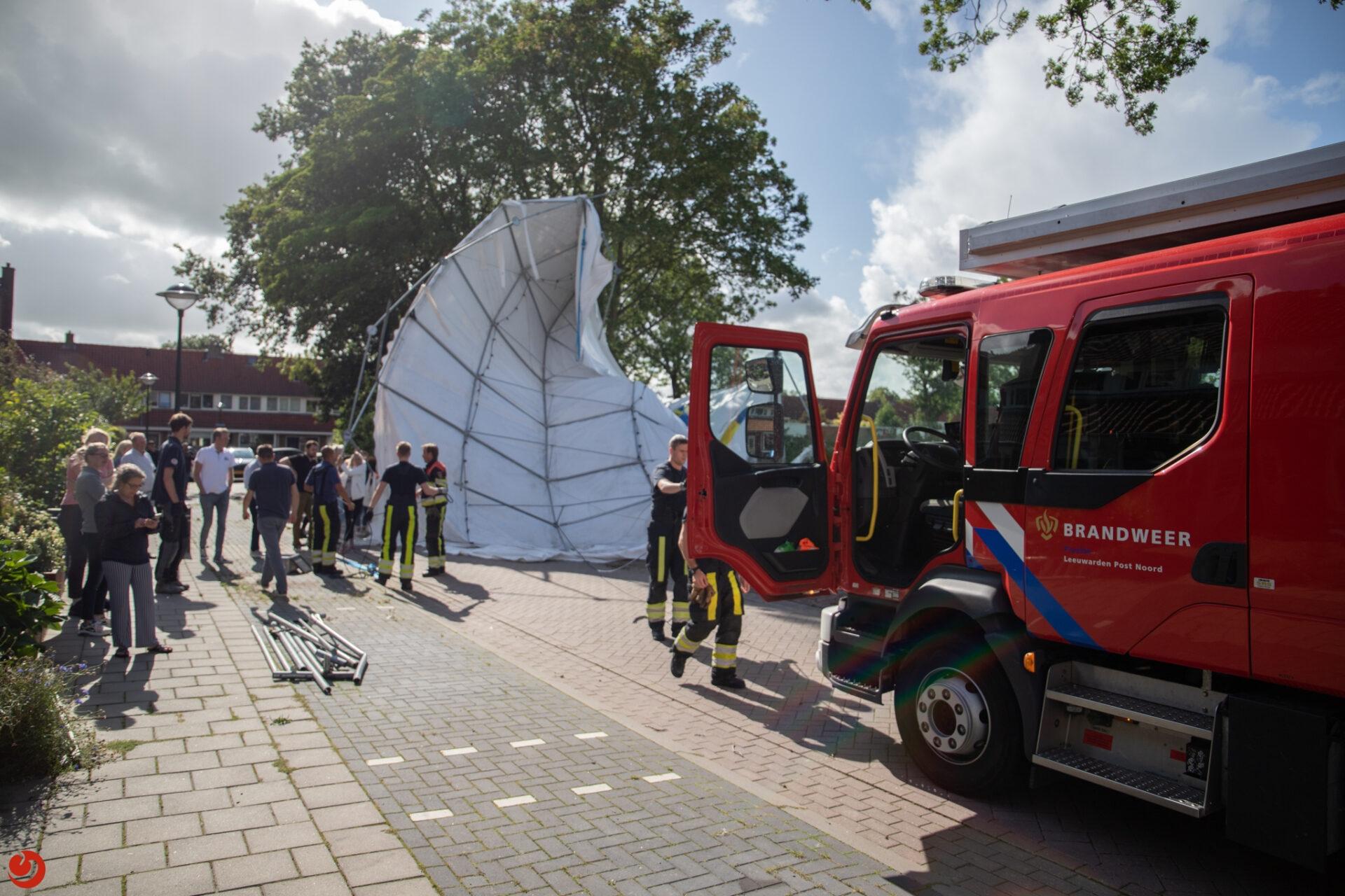 Grote tent waait de straat op door harde wind in Leeuwarden
